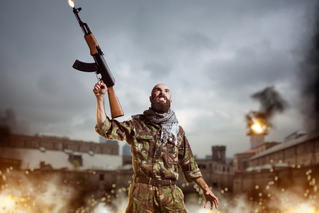 Terrorist with rifle stands in explosion and fire