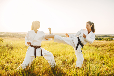 Two female karate in kimono fight in summer field Banque d'images