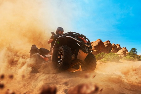 Quad bike rider climbing the sands in quarry, front view, dust clouds. Male driver in helmet on atv, offroad in sandpit Stock Photo