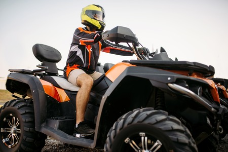 Rider in helmet and equipment on quad bike, front view, closeup. Male quadbike driver, atv riding
