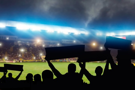 Group of football fans on tribune are cheering for their team victory, back view, crowd of people silhouettes with hands up holds slogans and banners on sport arena Imagens