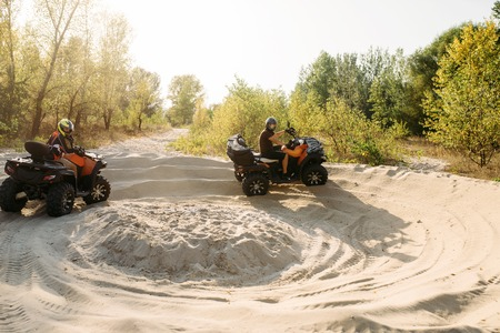 Two atv riders in helmets running laps on sand