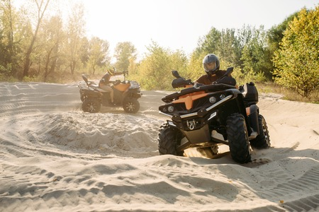 Two atv riders in helmets ride in a circle on sand Imagens
