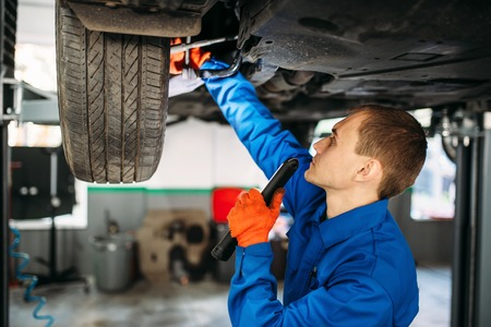 Mechanic with lamp checks the car suspension Stock Photo