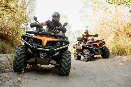 Deux coureurs de quad voyage en forêt, vue de face