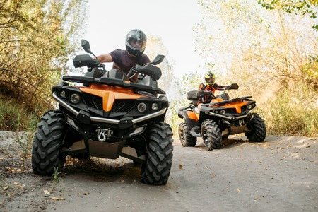 Due motociclisti in quad viaggiano nella foresta, vista frontale