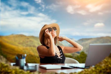 Frau am Bürotisch denkt an eine Reise Standard-Bild
