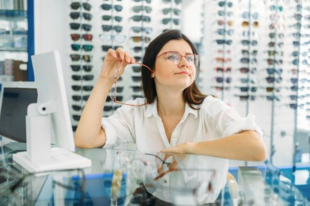 Female optician and consumer chooses glasses frame Stock Photo