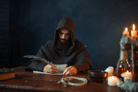 Medieval monk sitting at table and write, top view Stock Photo