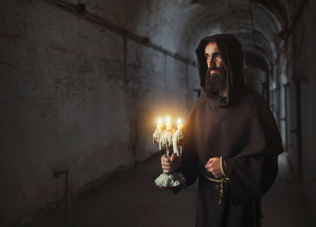 Medieval monk in robe holds a candlestick in hands Stock Photo