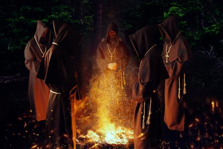 Monjes medievales rezando contra un fuego en la noche Foto de archivo