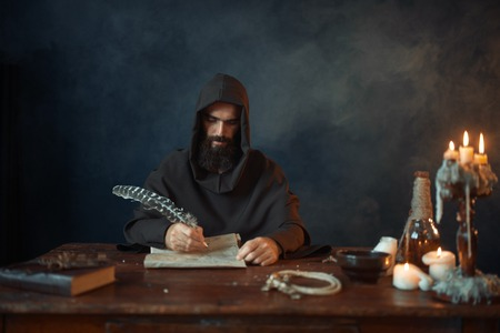 Medieval monk in robe writes with a goose feather Stock Photo