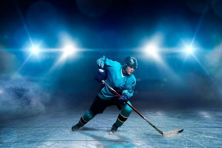 One hockey player on ice, spotlights on background