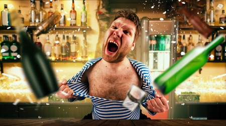 Drunk bartender tears his vest at the bar counter Stockfoto