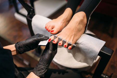 Pedicure master in gloves polishes nails with file