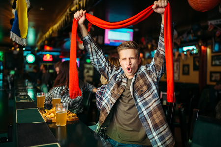 Fan raises his hands up at counter in sports bar