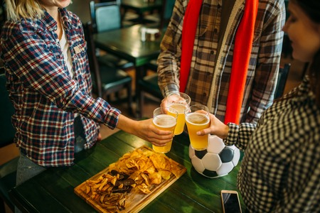 Football fans clink glasses with beer in sport bar