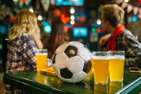 Ball and beer on the table in sports bar