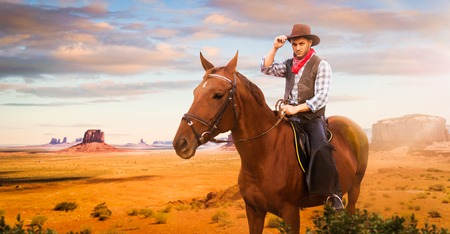 Cowboy riding a horse in desert valley, western 写真素材 - 113200406