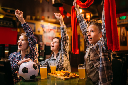 Football fans raise their hands up in sports bar