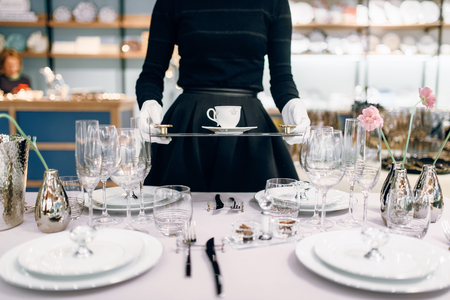 Waitress with tray puts the dishes, table setting 免版税图像