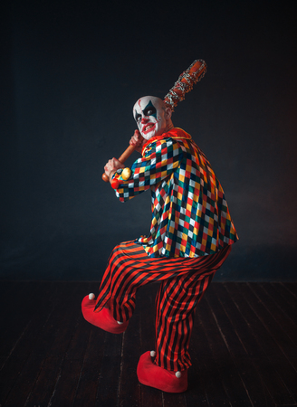 Scary bloody clown reaches out baseball bat Фото со стока