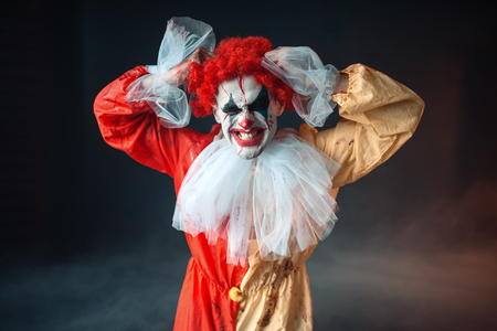 Scary bloody clown tears his hair, jerk in anger Banco de Imagens