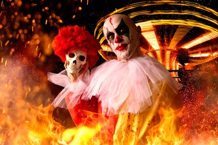 Payaso loco con sangre sostiene un cráneo humano, parque de atracciones
