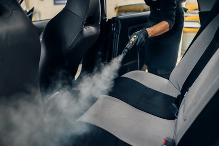 Carwash, worker cleans seats with steam cleaner 免版税图像 - 115161160