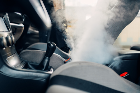 Dry cleaning of car interior with steam cleaner