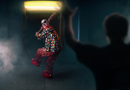 Bloody clown with baseball bat against his victim Standard-Bild