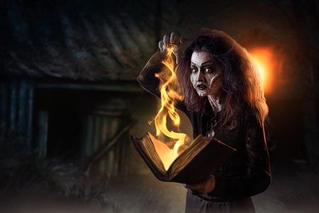 La bruja sostiene el libro de hechizos, poderes oscuros de la brujería