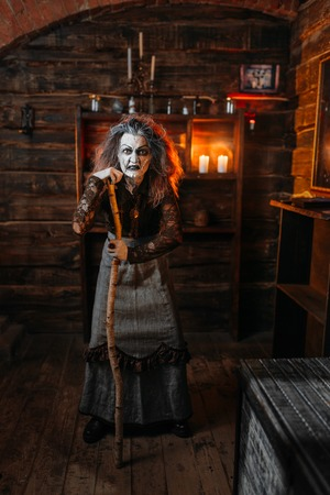 Scary witch stands leaning on a cane, seance