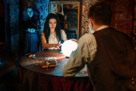 Couple on spiritual seance, witch on background Imagens