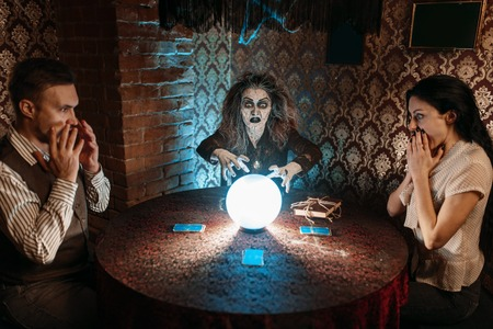 Witch reads scary spell over a crystal ball Banco de Imagens