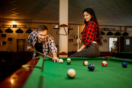 Couple plays in billiard room, male player aiming Stock Photo