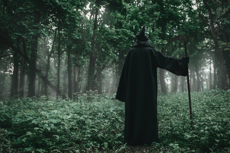 Death in a black hoodie with a scythe in forest Imagens