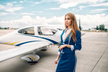 Smiling stewardess in suit against small airplane