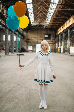 Anime style girl poses with colorful air balloons Фото со стока