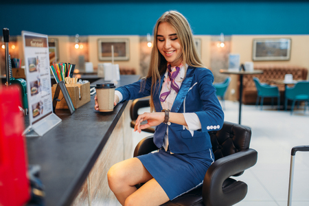 Stewardess drinks coffee in airport cafe