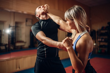 Kobieta na treningu samoobrony z trenerem
