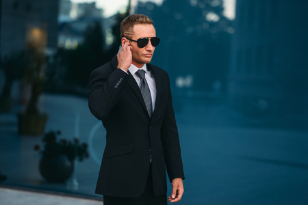Male bodyguard uses security earpiece outdoors Standard-Bild