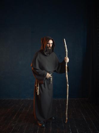 Medieval monk in robe with hood rests on a stick Zdjęcie Seryjne