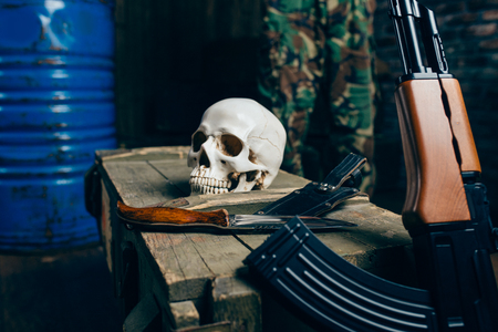 Skull, bomb, knife and rifle on box of ammunition Archivio Fotografico