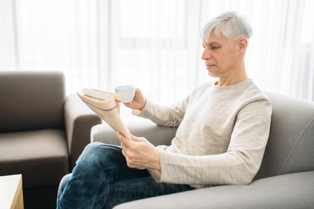 Adult man sitting on couch and reading newspaper Stockfoto