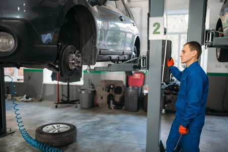 Mechanic with wrench looks at the car on lift