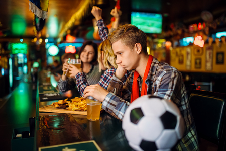 Upset football fan at the counter in sports bar