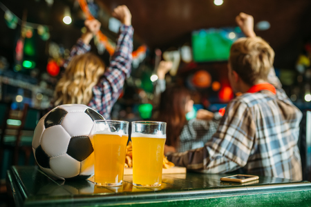 Ball and beer in sports bar, game watching concept Imagens