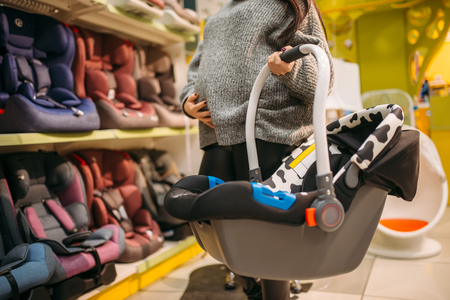 Pregnant woman with portable bed in store