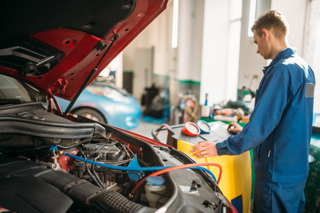 Mechanic pumps freon into the conditioning system Stock Photo